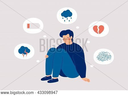 Sad Man Who Suffers From Mental Health Illness Is Sitting On The Floor. Boy Surrounded By Symptoms O