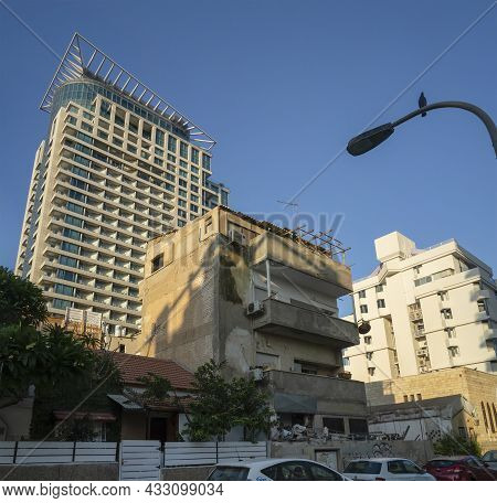Tel Aviv, Israel - August 20th, 2021: An Old, Neglected Building Among Modern Buildings On A Tel Avi