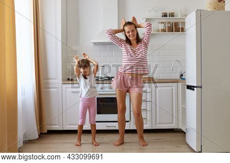 Child Daughter And Mom Having Fun In The Kitchen At Home, People Wearing T Shirts And Shorts, Dancin