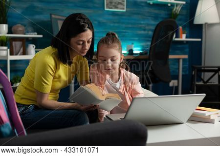 Mother Assisting Little Child On Reading School Book While Sitting At Home. Smart Girl With Modern L