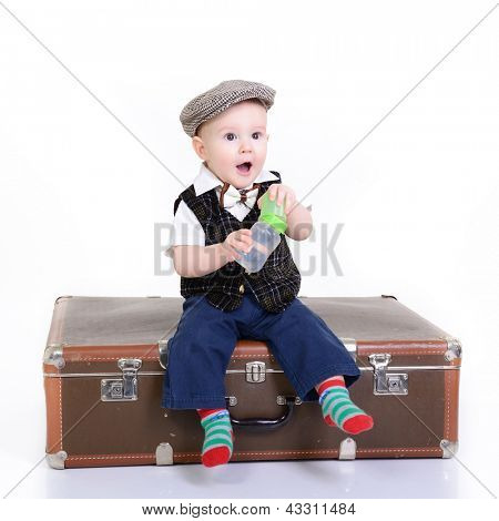 portrait of little baby boy sitting on old vintage suitcase, retro stylization of 30-50s poster