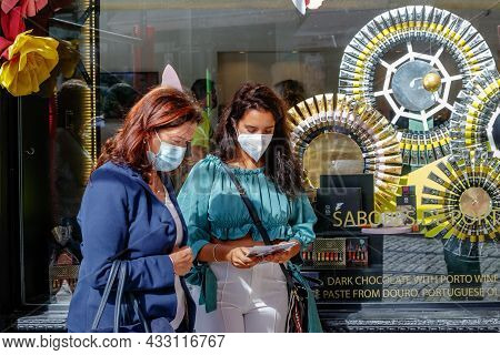 Porto, Portugal - September 11, 2021: Women In Protective Masks Walk On A Street In The Center Of Po
