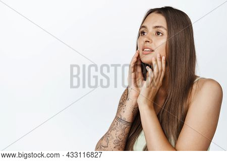Portrait Of Young Glamour Girl With Healthy Skin And Hair, Touching Her Face With Makeup, Looking As