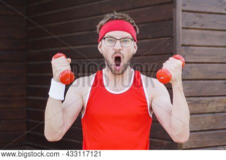 Portrait Of Funny Geek Exercising And Doing Sport Training. Crazy Athletic Man In Red Sportwear Usin