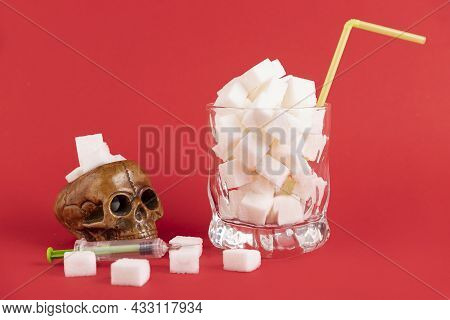A Glass Of White Glass With A Straw, Filled With White Cubes Of Refined Sugar And A Human Skull On A