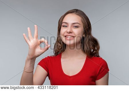 Excellent Job. Attractive Young Brunette Woman In Red T Shirt Showing Ok Sign And Smiling Satisfied,