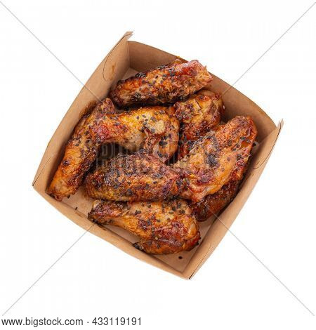 Portion of chicken wings in sauce with sesame seeds in a cardboard box isolated on white background, top view. Template for designers.