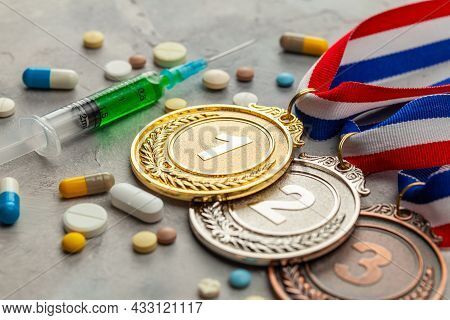Doping For Athletes. Golds, Silver And Bronze Medal And Doping Syringe And Pills With Capsules On A