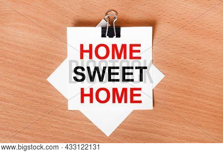 On A Wooden Table Under A Black Paper Clip Lies A Sheet Of White Paper With The Text Home Sweet Home