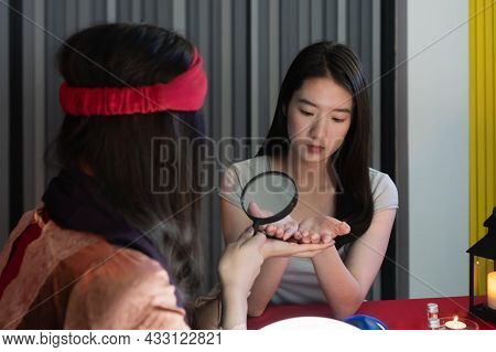 Attractive Beautiful Asian Woman Hands To Fortune Teller Use A Magnifying Glass To Read The Lines Of