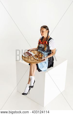 Studio Shot Of Attractive Woman, Waitress In Traditional Austrian Or Bavarian Costume Sitting With T