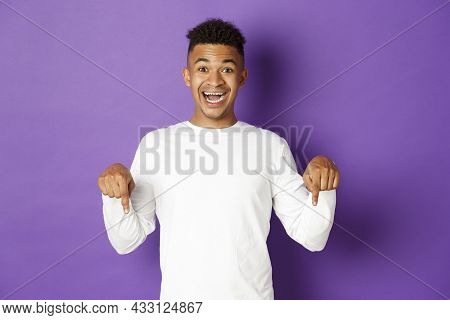 Portrait Of Handsome African-american Guy In White Sweatshirt, Pointing Fingers Down And Smiling Hap