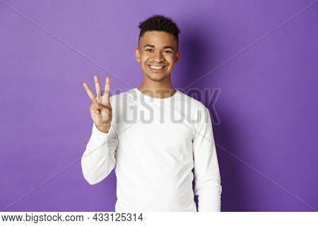 Image Of Cheerful African-american Guy In White Sweatshirt, Showing Three Fingers And Smiling, Stand