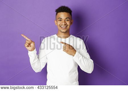Cheerful African-american Man In White Sweatshirt Showing Copy Space For Logo, Pointing Fingers Left