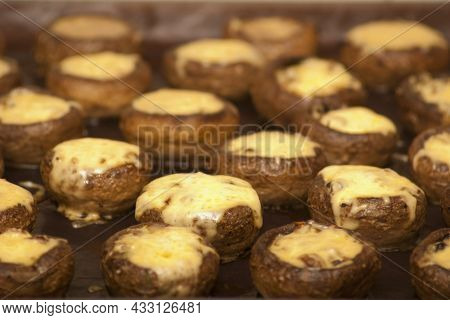 Champignons Stuffed With Cheese On A Baking Sheet