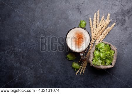 Lager beer mug, hops and wheat on old stone table. Top view flat lay with copy space