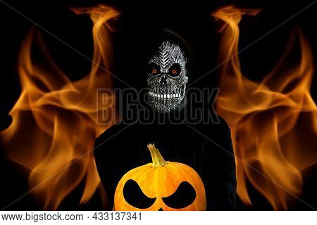Grim Reaper Holding Crop Halloween Pumpkin Head. Man In Death Mask With Fire Flame In Eyes And Grin