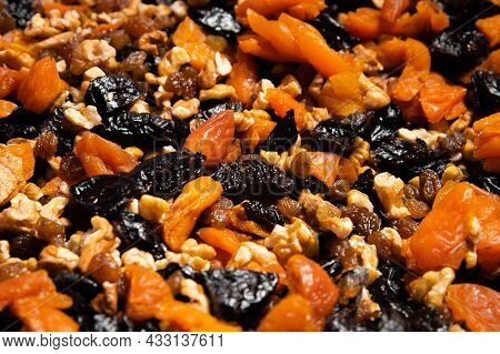 Dried Mixture Of Walnuts And Dried Fruits, Raisins, Grapes And Prunes Close-up. Mix For Adding To Ba