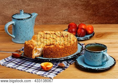 Homemade Pie With Nectarines And Cup Of Tea On Wooden Table. Shallow Focus.