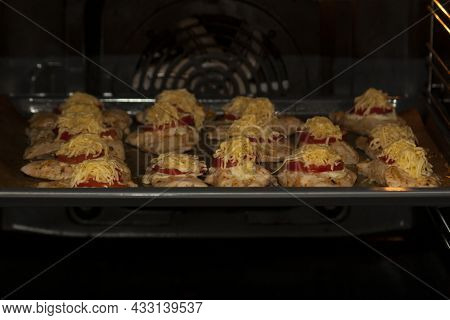 Cooking Chicken Meat In The Oven. A Baking Sheet With Chicken Pieces, Tomatoes And Cheese In The Ele