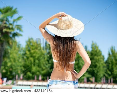Young woman holding her hat on the poolside