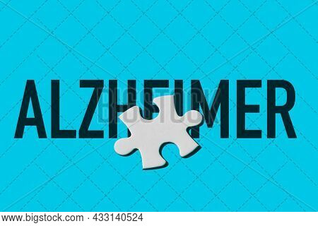 the world alzheimer and a blank white puzzle piece on a blue background