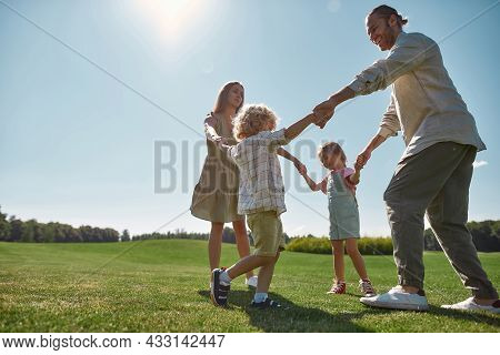 Full Length Shot Of Young Parents Holding Hands In Circle With Their Two Little Kids, Boy And Girl I