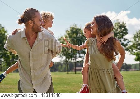 Young Parents Smiling At Each Other While Giving Piggyback Ride To Their Little Kids. Family Walking