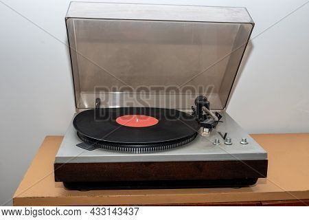 Analog Retro Vintage Stereo Turntable On A Wooden Table. An Old-fashioned Plastic Turntable Playing