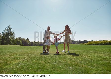 Active Parents Spending Time Together With Two Little Kids, Boy And Girl In Green Park On A Summer D