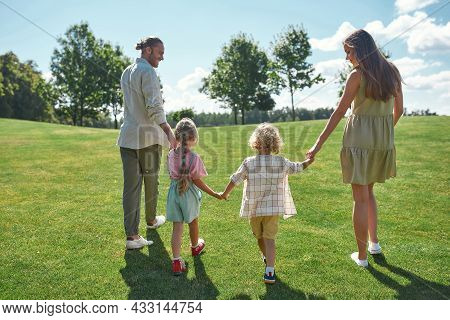 Back View Of Young Parents Holding Hands Together With Their Little Kids, Boy And Girl And Walking O