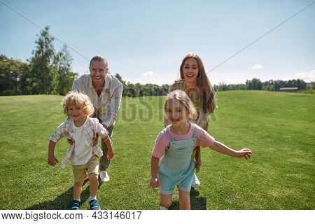 Joyful Young Parents Playing Catch Together With Two Little Children, Boy And Girl In Green Park On