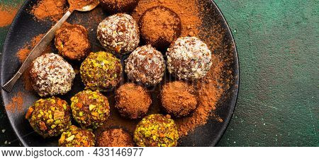 Variety Of Homemade Dark Chocolate Truffles With Cocoa Powder, Pistachios, Almonds In Dark Brown Bac