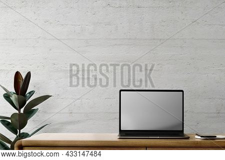 Laptop with blank screen on a desk loft home office zone design