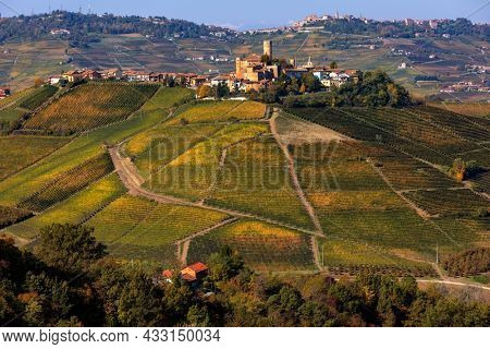 View of small medieval town on the hill with colorful autumnal vineyards in Piedmont, Northern Italy.