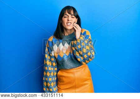 Young hispanic woman wearing casual winter sweater touching mouth with hand with painful expression because of toothache or dental illness on teeth. dentist