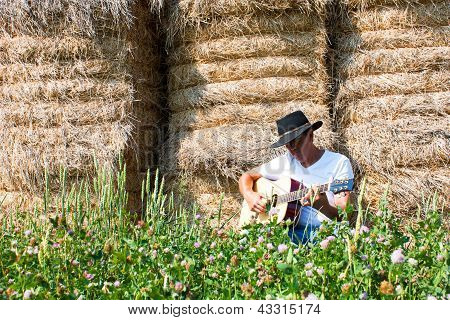 Cowboy By Haystack Plays Guitar Horizontal