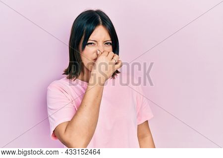 Young hispanic woman wearing casual pink t shirt smelling something stinky and disgusting, intolerable smell, holding breath with fingers on nose. bad smell