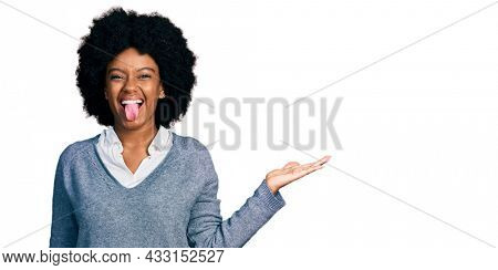 Young african american woman presenting with open palm sticking tongue out happy with funny expression.
