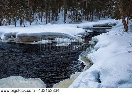 Stormy Non-freezing River In A Winter Snowy Forest. Winter Landscape, Karelia