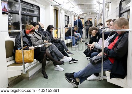 Moscow, Russia - September 2021: People In A Metro Train In Autumn, Passengers In Masks Sits With Sm