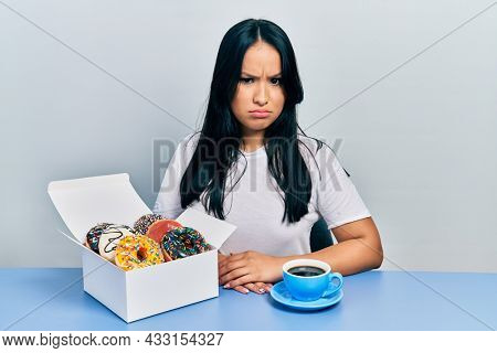 Beautiful hispanic woman with nose piercing eating doughnuts and drinking a cup of coffee skeptic and nervous, frowning upset because of problem. negative person.