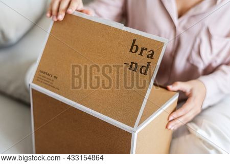 Woman unpacking brown box in the living room