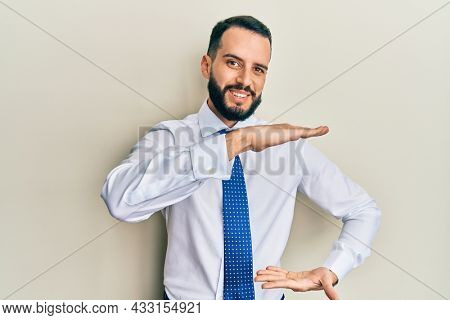 Young man with beard wearing business tie gesturing with hands showing big and large size sign, measure symbol. smiling looking at the camera. measuring concept.