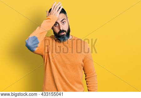 Hispanic man with beard wearing casual winter sweater surprised with hand on head for mistake, remember error. forgot, bad memory concept.