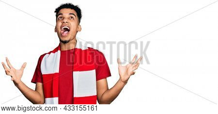 Young african american man football hooligan cheering game crazy and mad shouting and yelling with aggressive expression and arms raised. frustration concept.