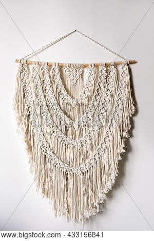 Vertical View Of Neat Handmade Macrame Hanging On Wooden Plank At White Wall In Bright Room. Concept