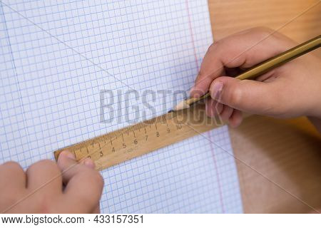 The Student Draws A Figure In A Notebook With A Pencil Along A Ruler. A Schoolboy Performs A Task At