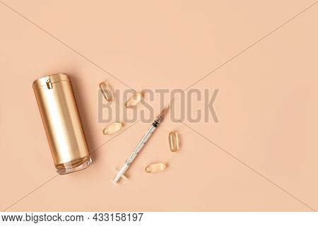 Beautiful Composition Of Gold Mockup Cosmetic Bottle, Syringe And Vitamin Capsules On Pastel Backgro