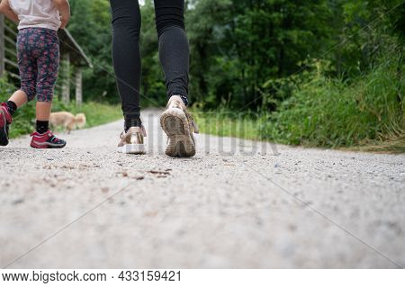 Low Angle View Of A Woman And Her Toddler Daughter Walking On A Footpath In Green Nature.